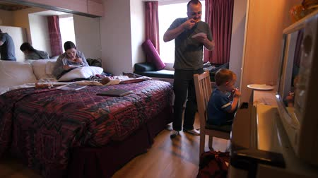 mrożonki : A young family cooks frozen pizzas for dinner in a hotel room microwave