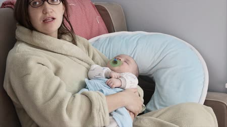 мать : A tired young mother rocks her newborn baby boy to sleep in his bedroom