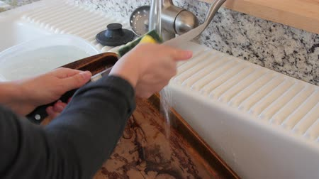 spoons : Young woman cleans a knife and dishes in the sink Stock Footage
