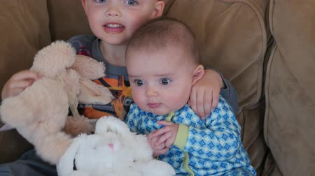 çikolata : Little boys on easter morning with their stuffed bunnies on a couch in their home Stok Video