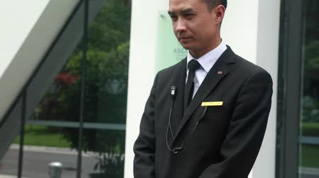отель : a doorman in china ready to open the car door at a hotel as passengers get out of the car Стоковые видеозаписи