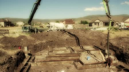 яма : Construction workers prepare and pour the footings of a house.