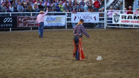 chapéu : A cowboy picks up his hat after falling off a bucking horse at a national PRCA rodeo Vídeos