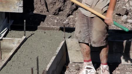 pompki : Construction workers prepare and pour the footings of a house.