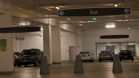 общественный : Cars parked in a parking garage beneath a mall