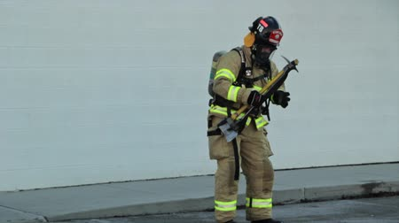 fire suit : firefighters putting out a fire at a warehouse Stock Footage