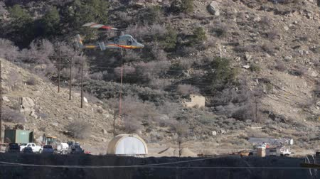 kabel : A helicopter carrying construction supplies through a desert mountain landscape in Utah