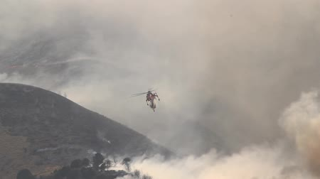bush fire : A helicopter battles a gigantic wildfire on a dry mountainside, dropping hundreds of gallons of water on the flames. Stock Footage