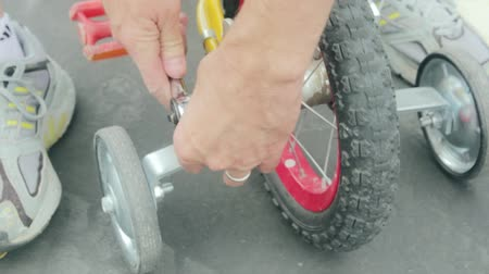 rowerek : a father puts training wheels on his toddlers bicycle Wideo