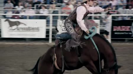 buty : Riding a saddle bronc at the rodeo