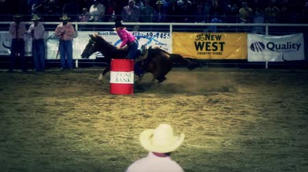 chapéu : Professional cowgirls barrel racing in a national PRCA rodeo