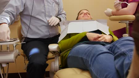 ból zęba : A dentist working on a womans teeth in a chair Wideo