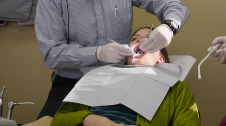 stomatologia : A dentist works on a woman in his chair Wideo