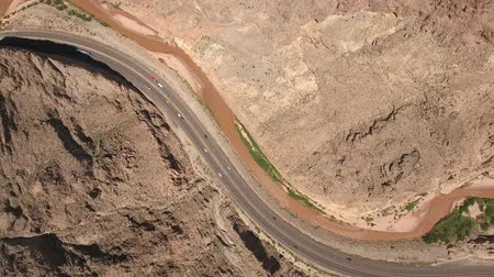 A descending aerial shot of cars driving in a desert canyon by river Стоковые видеозаписи