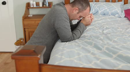 ajoelhado : A dolly shot of a man praying by his bedside