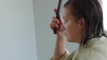 tüyler : A dolly shot of a woman brushing wet hair in a robe Stok Video