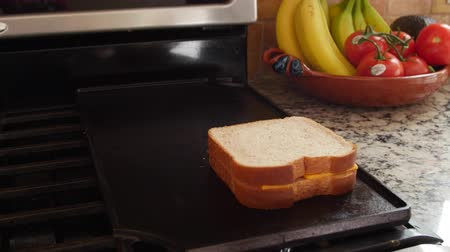 cozinhar : A dolly shot of a woman cooking grilled cheese sandwiches