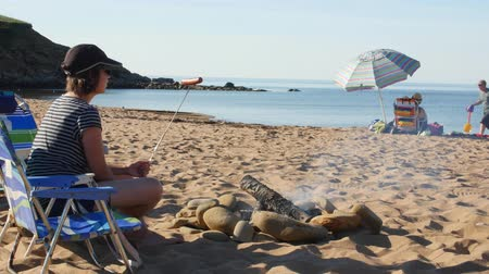 cape breton : A family roasting hotdogs for dinner on beach