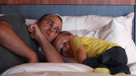 colchão : A father and boy in bed at a modern hotel room