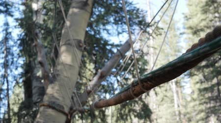 the suspension bridge : A gimbal shot of a rope monkey bridge at a scout camp Stock Footage