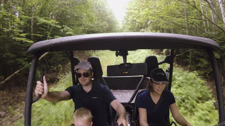 gyújtás : A family riding side by side four wheeler in thick forest