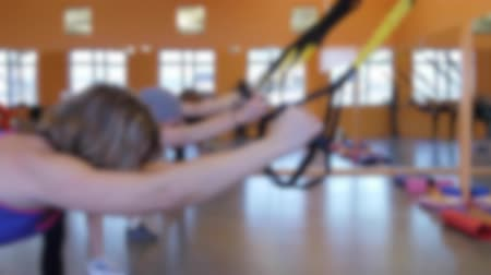 kolano : A group doing TRX training in a gym