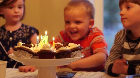 queque : A little boy blows out candles on cupcakes for birthday