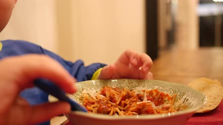spagetti : A little boy eats a bowl full of spaghetti for dinner