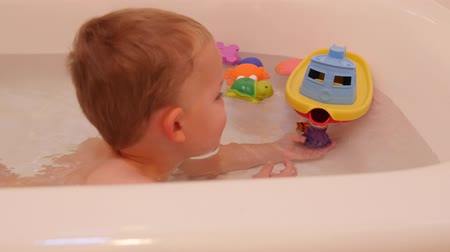 tuvalet : A little boy in bathtub with toys Stok Video