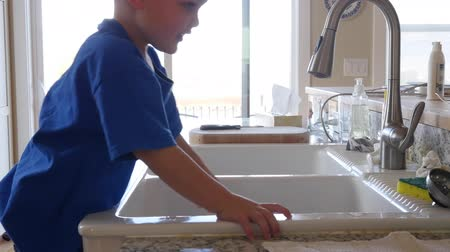 gąbka : A little boy playing in the kitchen sink with the water