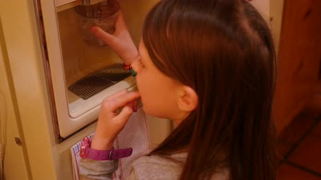 refrigerador : A little girl fills her cup with water from the fridge