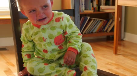 A little toddler cries after being put on time out chair Stock Footage