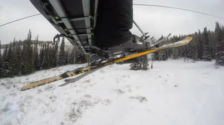 esqui : A low shot of skis on a ski lift going up mountain