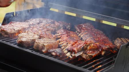 A man barbecues ribs and steak for summer party Stock Footage