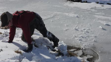 fishermen : A man breaks through ice on pond