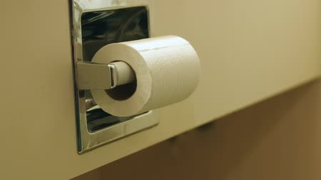 enrolado : A man grabs toilet paper while using the bathroom in a hotel