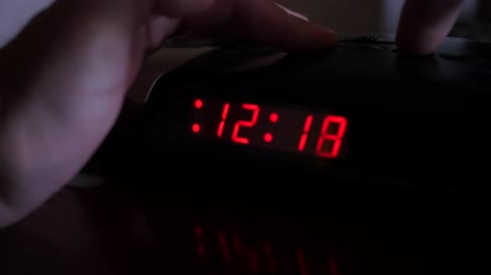 acorde : A man sets digital alarm clock time
