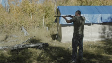 A man shooting a rifle while camping