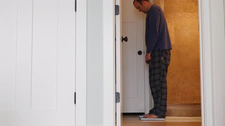 baixo teor de gordura : A man steps on a bathroom scale to weigh himself Stock Footage