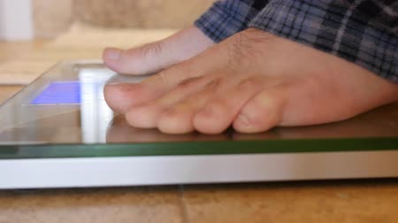 baixo teor de gordura : A mans feet step on scale to weigh himself Stock Footage
