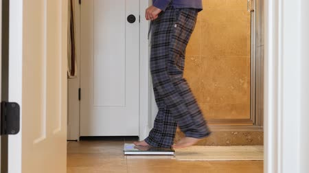 baixo teor de gordura : A mans steps on a bathroom scale to weigh himself
