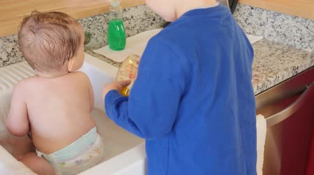tubérculo : A mother giving a baby a bath in kitchen sink after throwing up