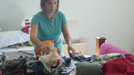 домохозяйка : A mother sorting through her kids clothes