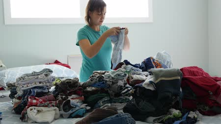 домохозяйка : A mother sorts through the kids clothes