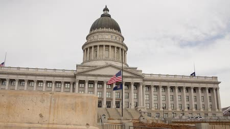 flag half mast : A slow Motion Dolly shot of flags at the Utah State Capitol Building Stock Footage