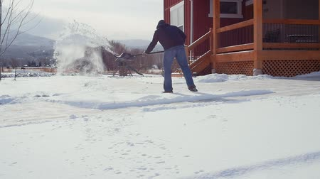 vyčerpaný : A slow motion shot of man shoveling snow from his driveway