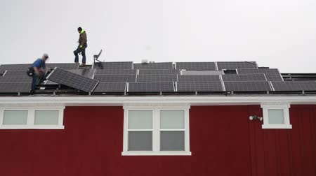 fotovoltaik : A timelapse of crews placing solar panels on the roof of a house