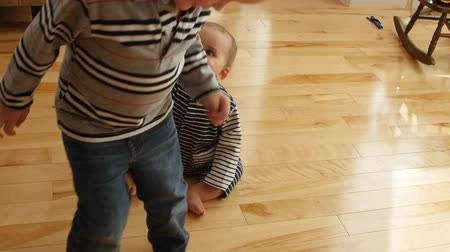 pažba : A toddler walking in circles around his baby brother