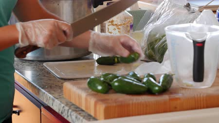 кинза : A woman chopps jalapenos for fresh salsa