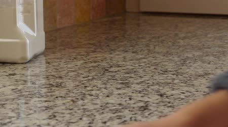 домохозяйка : A woman cleans the kitchen granite counter